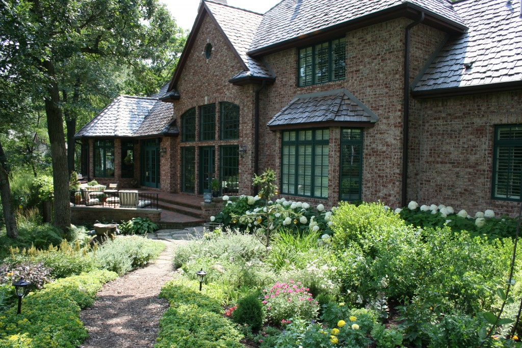 While this large home in a Twin Cities suburb hardly qualifies as a cottage, the cottage garden sensibility is in this garden space.