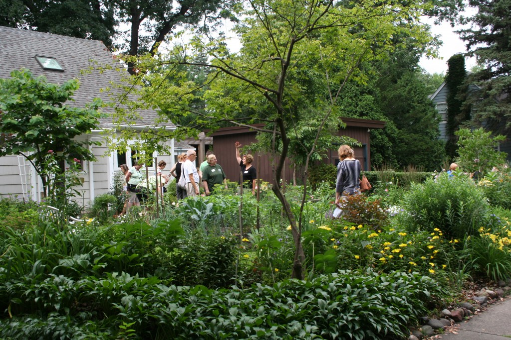 Tour goers check out a lush garden in front of a Minneapolis cottage.