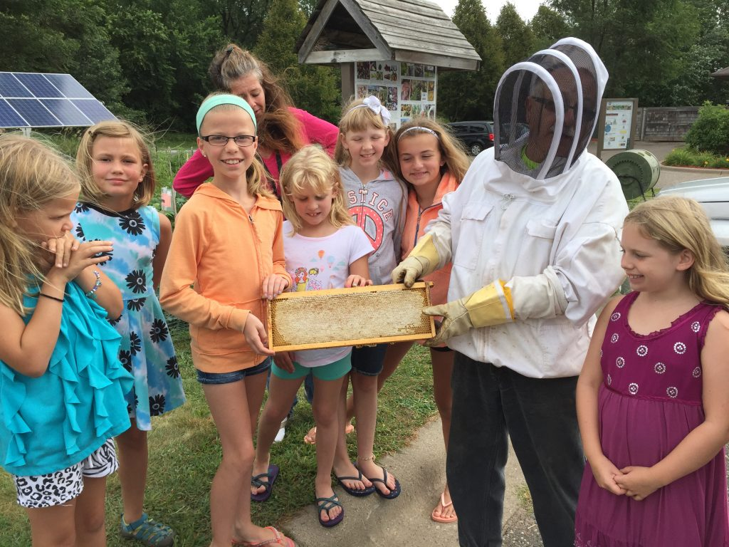 BeekeeperA.J. Moses brings beehives to the garden to teach children about pollinators and honey, which is harvested and donated to the food shelf.