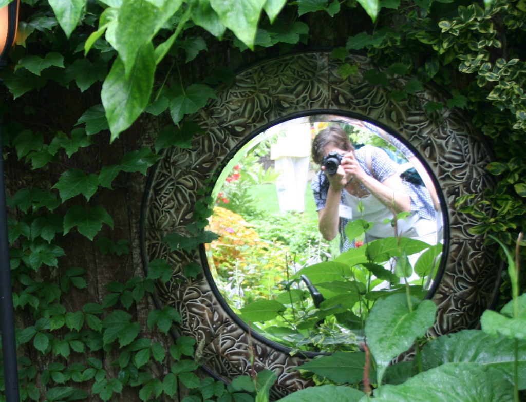 woman taking picture of mirror in garden