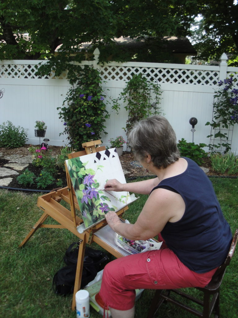 artist painting clematis on garden tour