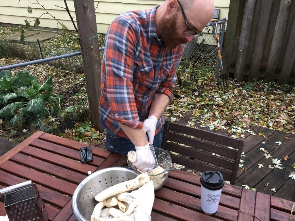 man grates horseradish root