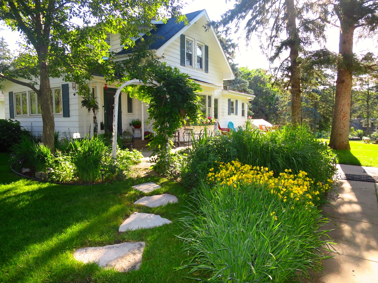 older yellow home with garden in front