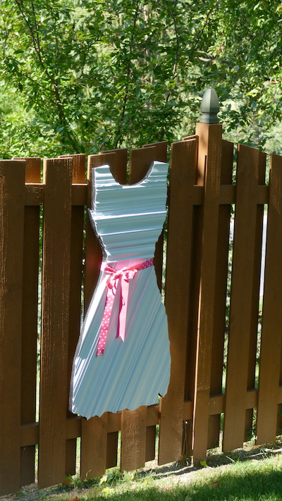dress art hung on brown fence